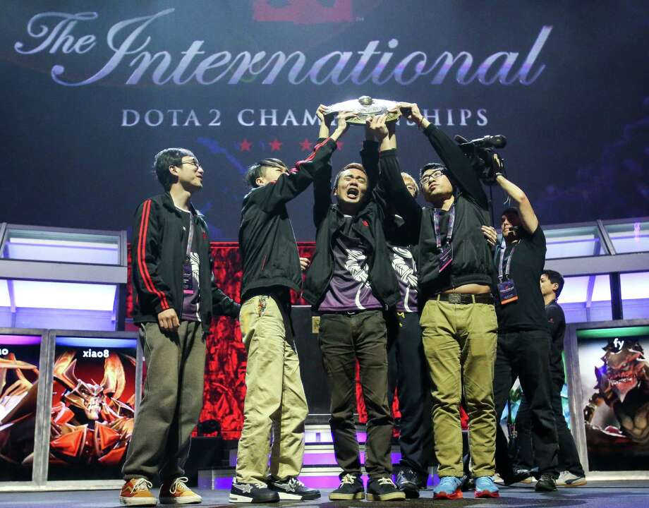 Team NewBee hoists the Aegis of Champions trophy after winning The International DOTA 2 Championships. Thousands packed KeyArena to watch The International DOTA 2 Championships on Monday, July 21, 2014. The Chinese team NewBee took home the Aegis of Champions after beating Vici Gaming in three out of four games. Photo: JOSHUA BESSEX, SEATTLEPI.COM / SEATTLEPI.COM