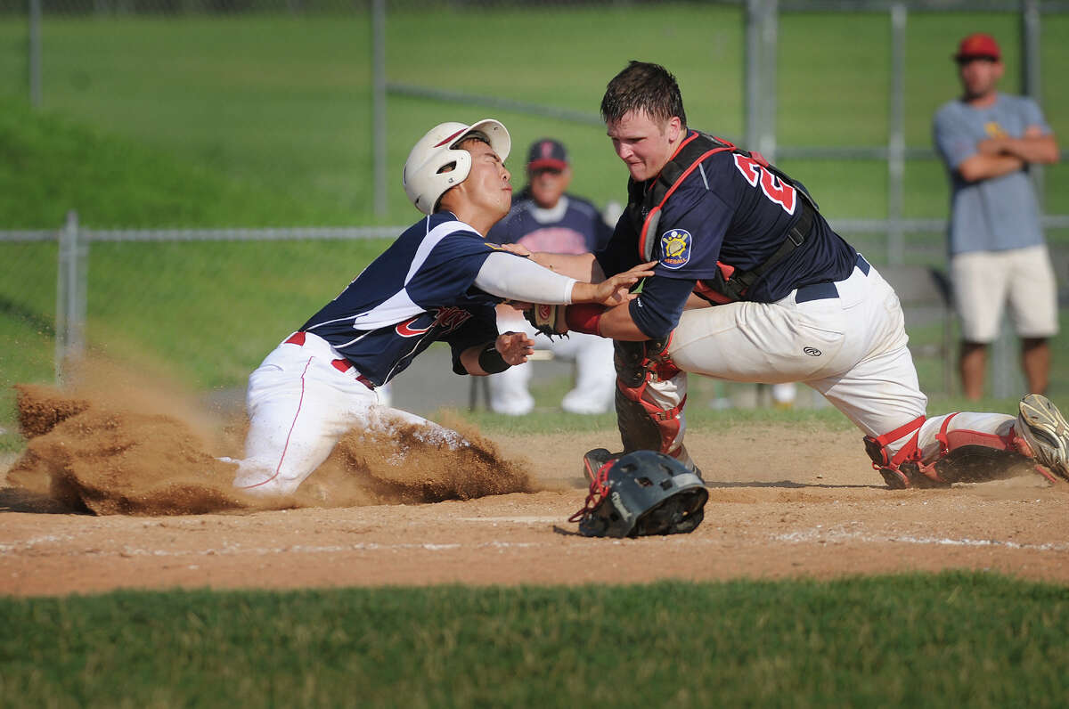 Greenwich's Ricky Okazaki, left, is tagged out by Trumbull Post 141 catcher Zach Sagar as Okazaki tried to score from first on a dropped fly ball in the 6th inning of Trumbull's 2-1 American Legion baseball victory at Trumbull High School in Trumbull, Conn. on Monday, July 21, 2014.