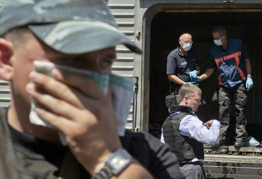 A man covers his face with a rag due to the smell as Netherlands forensic officials in Torez, Ukraine, inspect bodies from the crash site of Malaysia Airlines Flight 17. Photo: Vadim Ghirda / Associated Press / AP