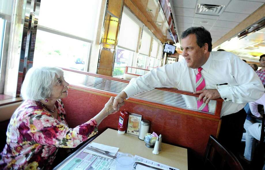 New Jersey Gov. Chris Christie center, kisses Paula Murray of Norwalk as Republican gubernatorial candidate Tom Foley, back center, and Mary Ann Springall, friend of Murray, looks on, during a visit to a diner, Monday, July 21, 2014 in Greenwich, Conn. Photo: Jessica Hill, AP / Associated Press