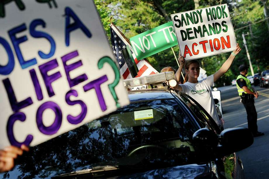 Eliza Eggleston of Newtown, Conn., right, holds up a sign outside a fundraising event for Republican gubernatorial candidate Tom Foley with New Jersey Gov. Chris Christie at a private residence, Monday, July 21, 2014, in Greenwich, Conn.  People lined the street to protest Christie's recent veto of legislation that would have reduced gun magazine capacities. Photo: Jessica Hill, AP / Associated Press