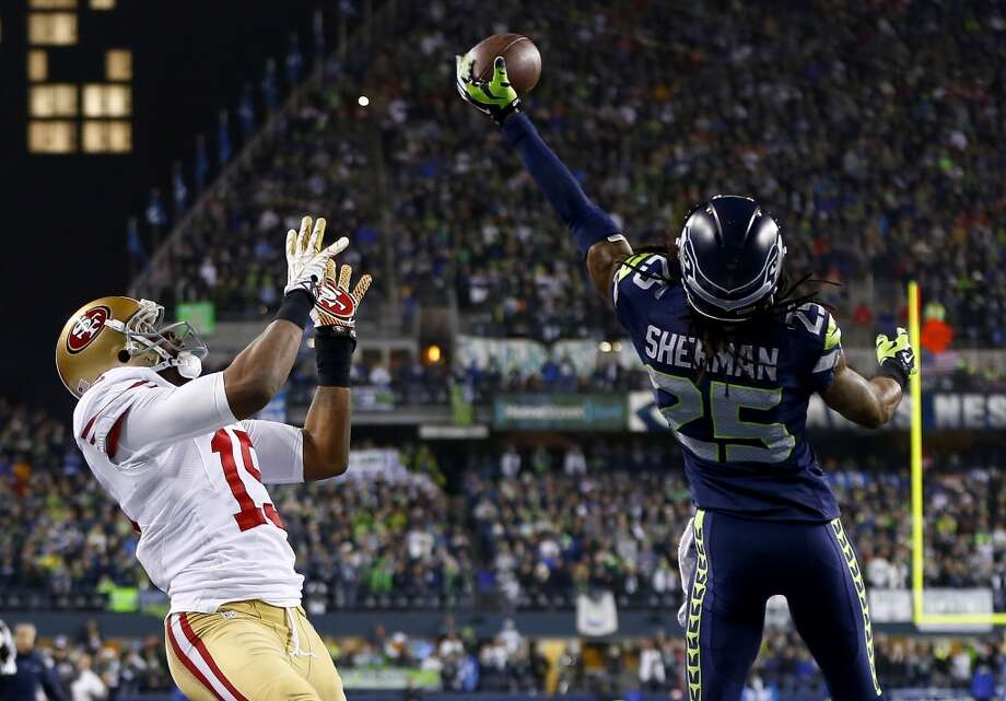 Richard Sherman of the Seattle Seahawks tips the ball up in the air before linebacker Malcolm Smith catches it to clinch the victory for the Seahawks against the San Francisco 49ers during the 2014 NFC championship game Jan. 19 at CenturyLink Field in Seattle.