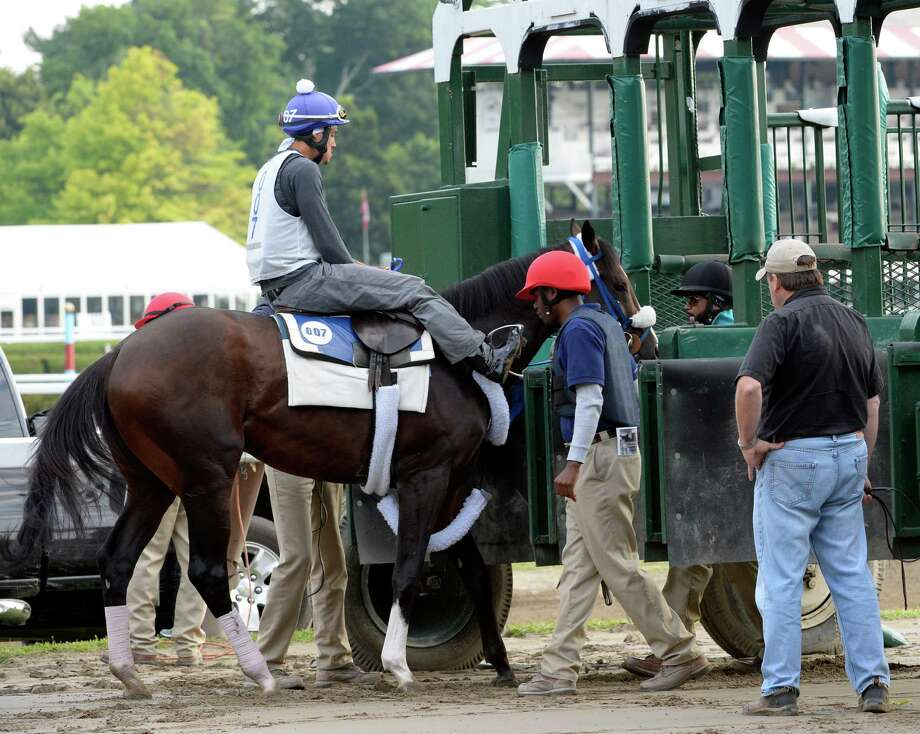 Trainer Jim Bond, right, waits for his Jim Dandy entrant Legend while he schools in the gate Monday morning, July 21, 2014, at Saratoga Race Course in Saratoga Springs, N.Y.  (Skip Dickstein / Times Union) Photo: SKIP DICKSTEIN