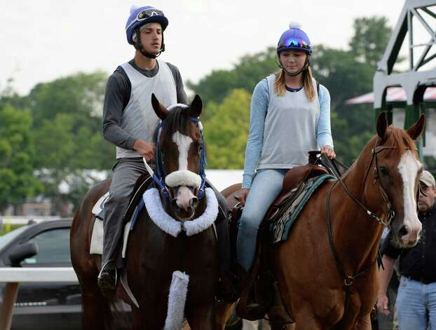 Jim Dandy entrant Legend, left, with exercise rider Omar Pereria in the saddle is lead from the gate after schooling by Allison Gomer on Chance Monday morning, July 21, 2014, at Saratoga Race Course in Saratoga Springs, N.Y. (Skip Dickstein / Times Union) Photo: SKIP DICKSTEIN