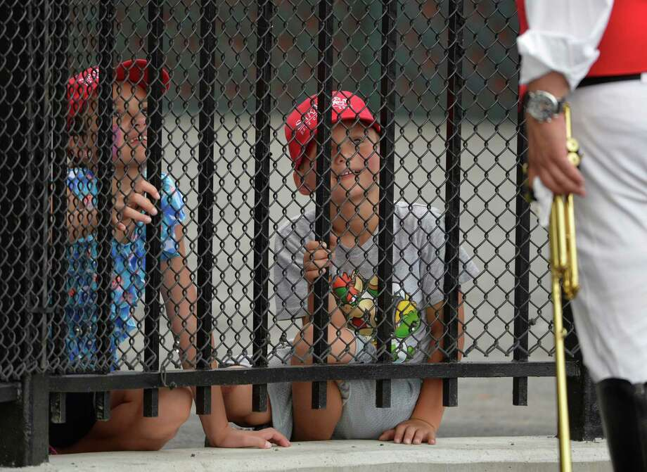Two young race goers are enthralled by Sammy the Bugler, right,  Monday afternoon July 21, 2014 at the Saratoga Race Course in Saratoga Springs, N.Y.         (Skip Dickstein / Times Union) Photo: SKIP DICKSTEIN