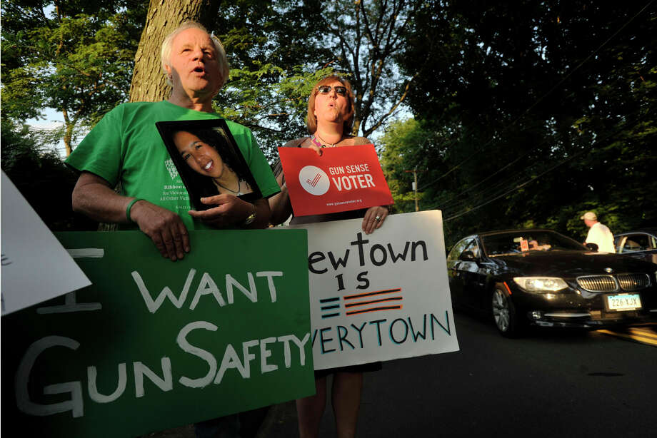 Nicholas Payne, left, of New Milford, and Kari Hulgaard, of Bethel, chant during a protest in Greenwich, Conn., on Monday, July 21, 2014. The activists were protesting New Jersey Governor Chris Christie's choice to veto a bill in New Jersey that would have limited the number of bullets allowed in a gun magazine. Christie was in Greenwich stumping for Republican gubernatorial candidate Tom Foley. Payne holds a photo of his daughter, Rebecca Payne, who was allegedly shot to death in Boston in 2008 by a drug dealer who went to the wrong house. Photo: Jason Rearick / Stamford Advocate