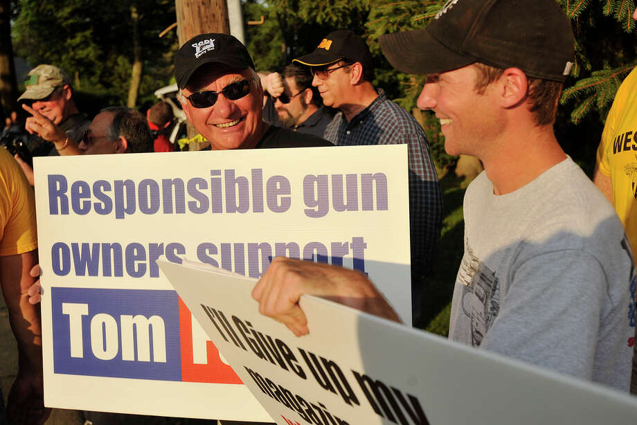 """Members of the Connecticut Citizens Defense League Julius Magyari Sr, left, and his son, Julius Magyari Jr, give a counterpoint to the gun control protesters across the street in Greenwich, Conn., on Monday, July 21, 2014. The activists were protesting New Jersey Governor Chris Christie's choice to veto a bill in New Jersey that would have limited the number of bullets allowed in a gun magazine. Christie was in Greenwich stumping for Republican gubernatorial candidate Tom Foley. The elder Magyari says he would be willing to talk with gun control activists, """"We have to stop the insanity."""" Photo: Jason Rearick / Stamford Advocate"""