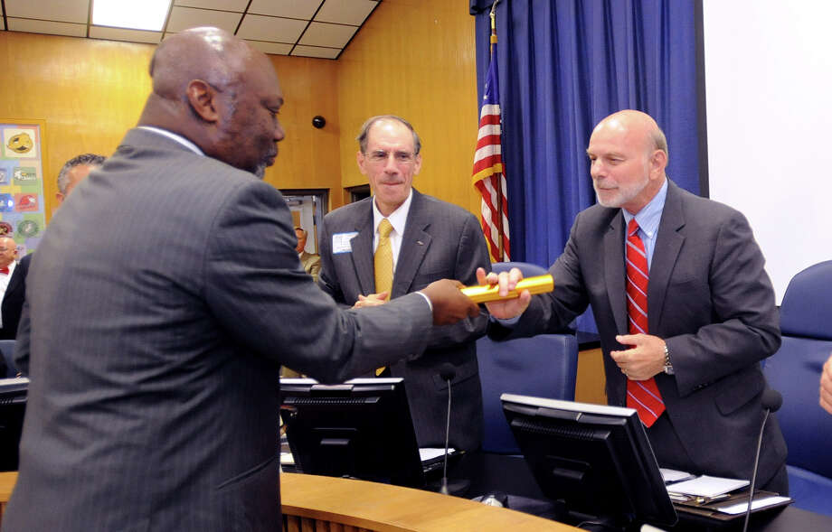 Michael Williams the commissioner of the Texas Education Agency hands a baton to Beaumont Independent School District's Interim Superintendent Vern Butler after the swearing in of a new board Monday night. The baton signified Williams turing the district over to the new board.