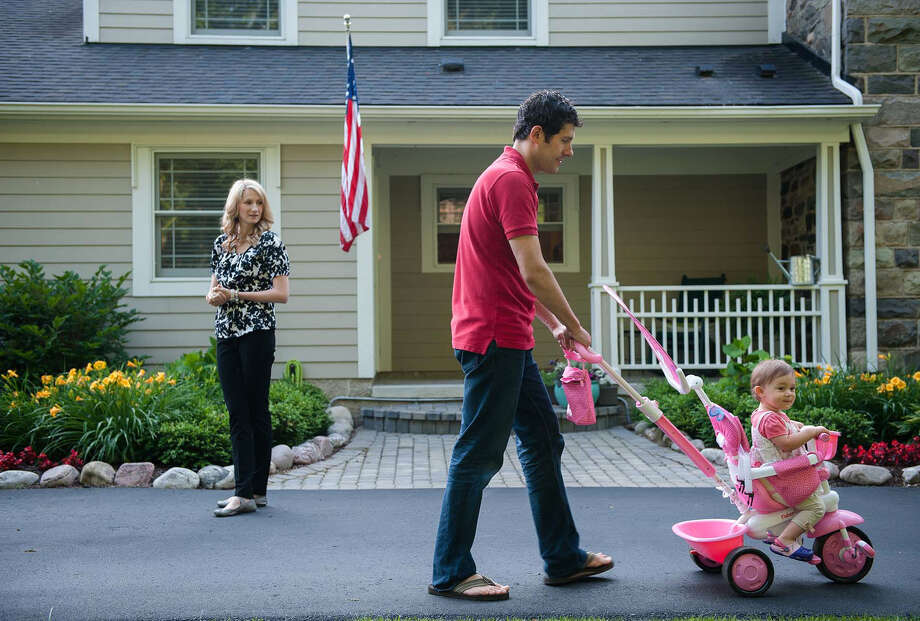 Marc Carlson pushes 14-month-old daughter Rebecca in her stroller as his wife, Diana Carlson, heads toward the car to go to work in West Bloomfield, Mich. Photo: James Fassinger / Washington Post / THE WASHINGTON POST