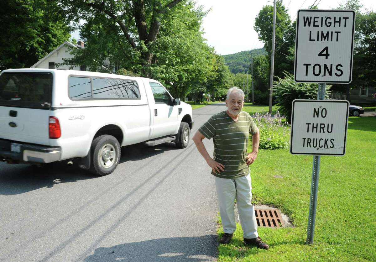 Bill Hornick stands by traffic signs at the end of Slingerlands Avenue where his home is on July 21, 2014 in Clarksville, N.Y. Hornick was once hit by a truck while mowing his lawn. Many trucks ignore the signs and he is trying to get the town to make some changes. (Lori Van Buren / Times Union)