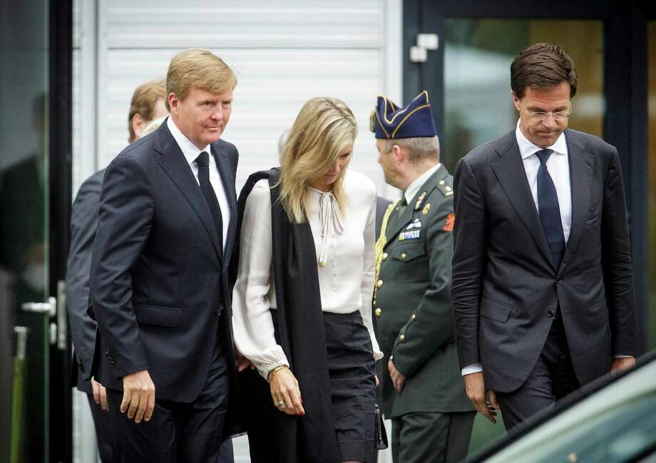 """Dutch King Willem-Alexander, left, Queen Maxima, center, and Dutch Prime Minister Mark Rutte, far right, leave a meeting in Nieuwegein, near the central city of Utrecht, Netherlands, Monday, July 21, 2014. Relatives of Dutch victims killed in the downing of Malaysia Airlines Flight 17 were meeting Monday afternoon with their king, queen and prime minister amid growing anger at the treatment of their loved ones' bodies by pro-Russian rebels in Ukraine. In an unusual move that underscored the severity of the national trauma, a somber King Willem-Alexander gave a brief televised address to his country after meeting grieving relatives. """"This terrible disaster has left a deep wound in our society,"""" the king said. """"The scar will be visible and tangible for years to come."""" (AP Photo/Phil Nijhuis) Photo: Phil Nijhuis, STR / AP"""