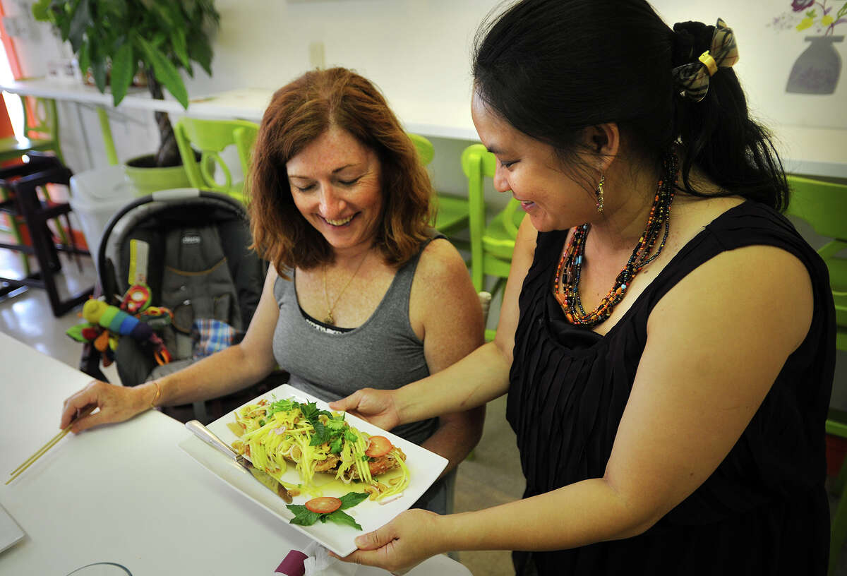 Mary Ann Provey, of Bridgeport, is served Pla Tod Yum Mamaung, crispy whole Red Snapper topped with spicy mango salad, by Dif McGeough at Ruuthai Kitchen authenthic Thai cuisine at 648 Beechwood Avenue in Bridgeport, Conn. on Tuesday, July 15, 2014.