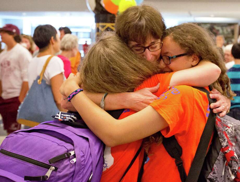 Relieved parent Wendy Suttin hugs her twin daughters, Beth and Sara, arriving back Monday from a three-week trip in Israel. The Suttin twins were part of a travel party of 48 from Houston's Congregation Emanu El that returned home. Unlike many other trips for Jewish American teens during the current conflict in the State of Israel, this traveling party taking part in the first Shirley Barish Memorial Israel trip - which includes five staff members and 43 students from the Congregation's Helfman Religious School - there were no plans of an early return. Photo: Billy Smith II, Staff / Houston Chronicle