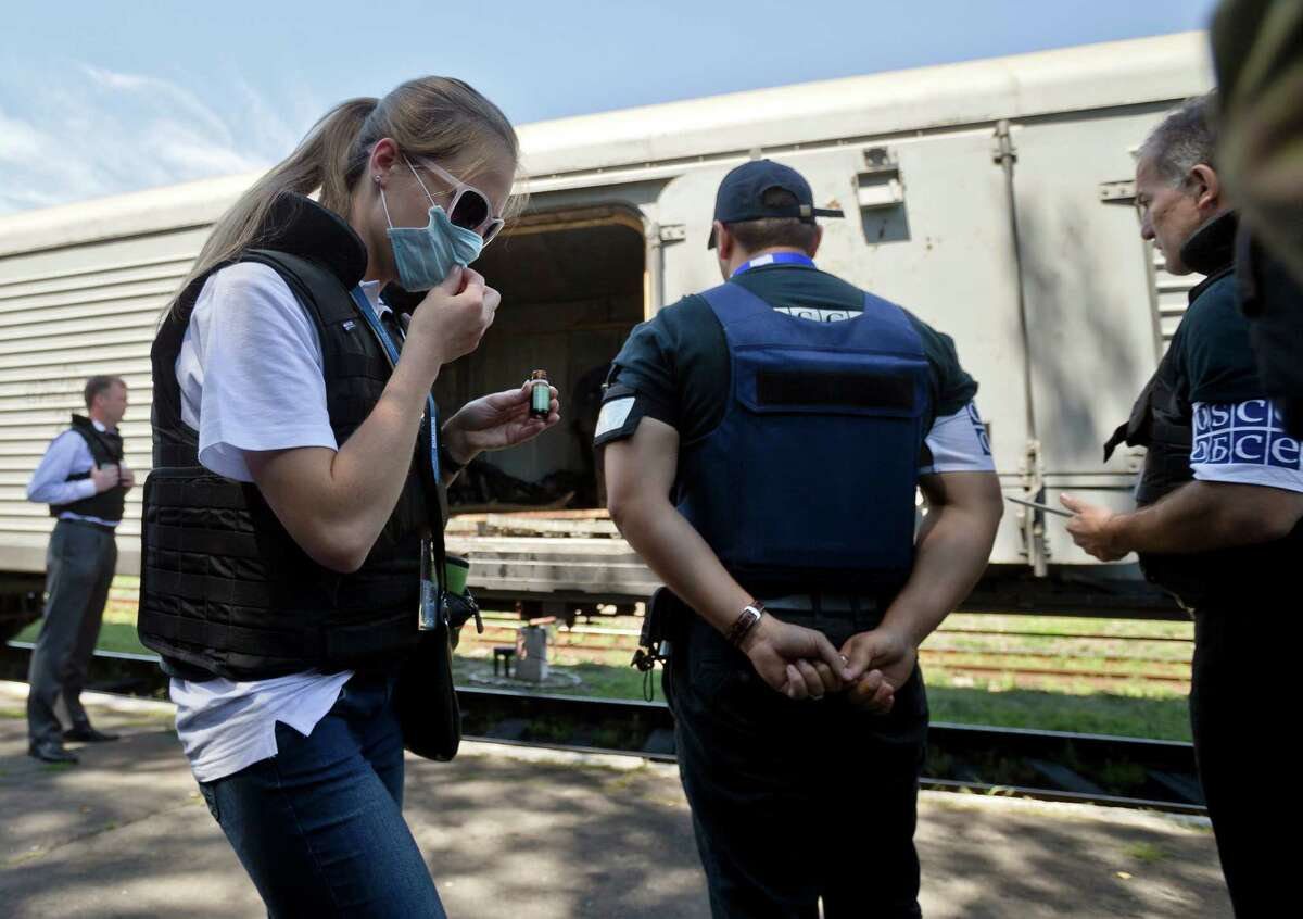 A members of the OSCE mission to Ukraine uses a chemical to combat the smell of decomposing bodies while inspecting along with Holland's National Forensic Investigations Team a refrigerated train loaded with the bodies of passengers in Torez, eastern Ukraine, 15 kilometers (9 miles) from the crash site of Malaysia Airlines Flight 17, Monday, July 21, 2014. Another 21 bodies have been found in the sprawling fields of east Ukraine where Malaysia Airlines Flight 17 was downed last week, killing all 298 people aboard. International indignation over the incident has grown as investigators still only have limited access to the crash site and it remains unclear when and where the victims' bodies will be transported. (AP Photo/Vadim Ghirda) ORG XMIT: XVG114
