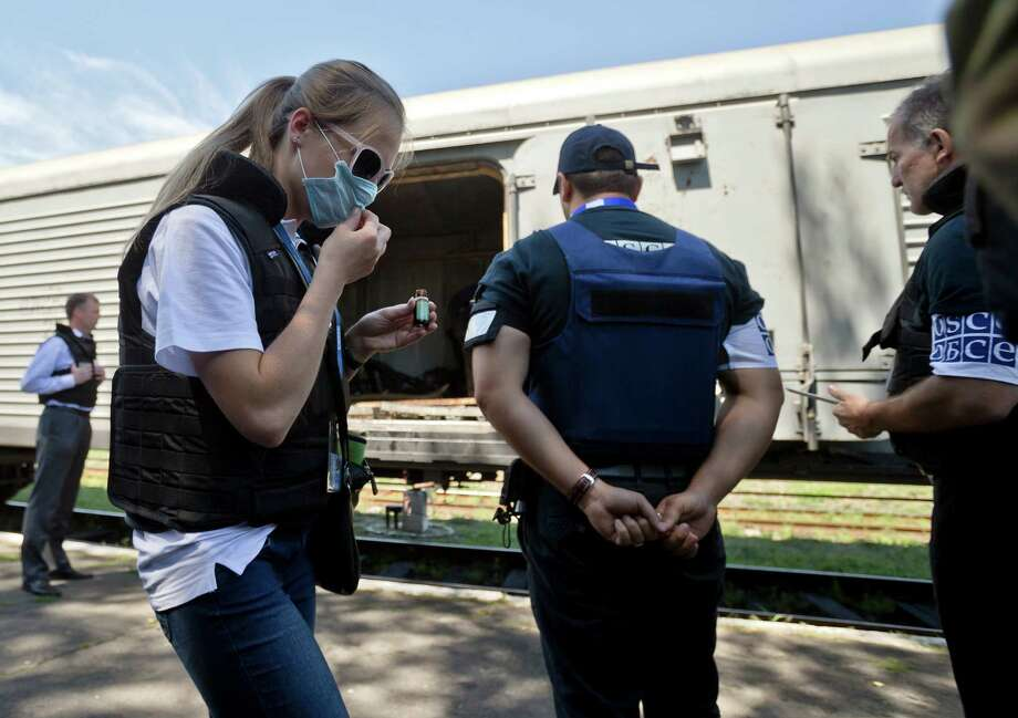 A members of the OSCE mission to Ukraine uses a chemical to combat the smell of decomposing bodies while inspecting along with Holland's National Forensic Investigations Team a refrigerated train loaded with the bodies of passengers in Torez, eastern Ukraine, 15 kilometers (9 miles) from  the crash site of Malaysia Airlines Flight 17, Monday, July 21, 2014. Another 21 bodies have been found in the sprawling fields of east Ukraine where Malaysia Airlines Flight 17 was downed last week, killing all 298 people aboard. International indignation over the incident has grown as investigators still only have limited access to the crash site and it remains unclear when and where the victims' bodies will be transported. (AP Photo/Vadim Ghirda) ORG XMIT: XVG114 Photo: Vadim Ghirda / AP
