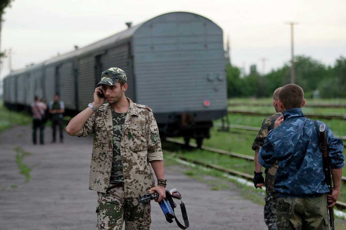 A pro-Russian rebel speaks on the phone as a refrigerated train loaded with bodies of the passengers departs the station in Torez, eastern Ukraine, 15 kilometers (9 miles) from the crash site of Malaysia Airlines Flight 17, Monday, July 21, 2014. Another 21 bodies have been found in the sprawling fields of east Ukraine where Malaysia Airlines Flight 17 was downed last week, killing all 298 people aboard. International indignation over the incident has grown as investigators still only have limited access to the crash site and it remains unclear when and where the victims' bodies will be transported. (AP Photo/Vadim Ghirda) ORG XMIT: XVG137