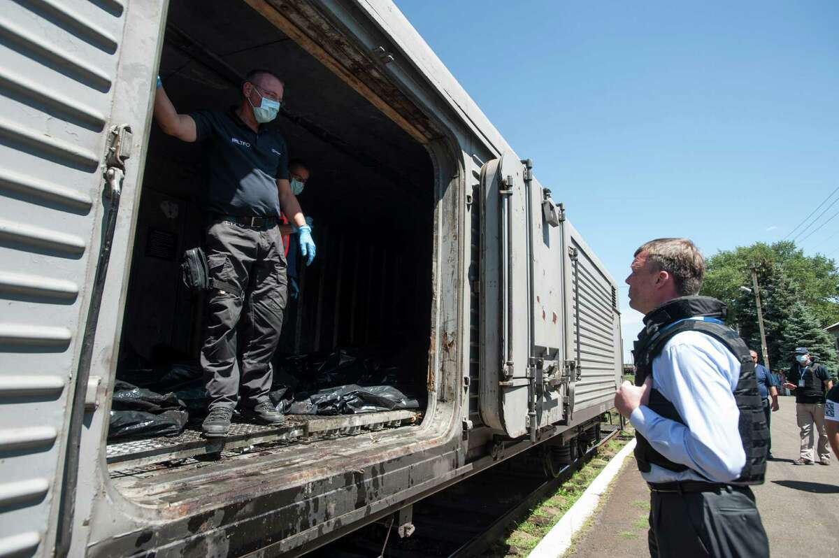 Deputy head of the OSCE mission to Ukraine Alexander Hug, right, speaks to a member of Netherlands' National Forensic Investigations team on the platform as a refrigerated train loaded with bodies of the passengers departs the station in Torez, eastern Ukraine, 15 kilometers (9 miles) from the crash site of Malaysia Airlines Flight 17, Monday, July 21, 2014. Another 21 bodies have been found in the sprawling fields of east Ukraine where Malaysia Airlines Flight 17 was downed last week, killing all 298 people aboard. International indignation over the incident has grown as investigators still only have limited access to the crash site and it remains unclear when and where the victims' bodies will be transported. (AP Photo/Evgeniy Maloletka) ORG XMIT: XAZ117