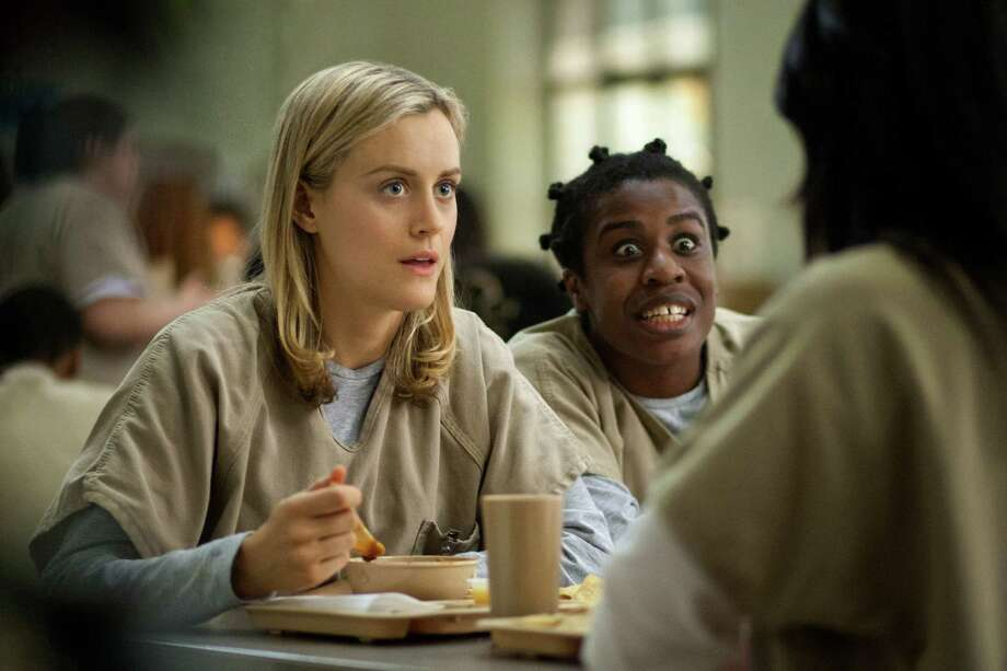 """Taylor Schilling and Uzo Aduba appear in a scene from the Netflix series """"Orange Is the New Black."""" The Los Gatos, Calif.-based company has been putting money into exclusive programming and original series. Photo: Paul Schiraldi, HONS / Netflix"""