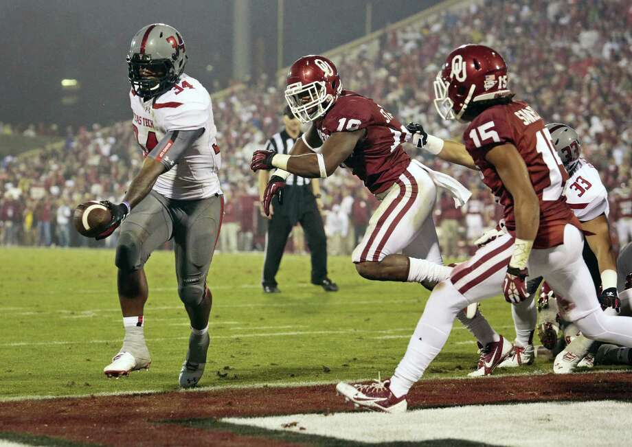 Texas Tech's Kenny Williams (left), scoring a TD against Oklahoma in 2013, may still receive some carries as a running back even though he is now starting at outside linebacker. Photo: Brett Deering / Getty Images / 2013 Getty Images