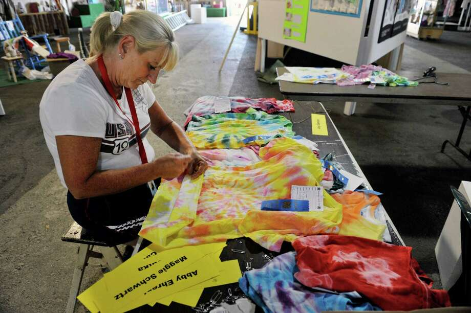 Cynthia Dort of Milton, a occupant protection educator for the Saratoga County Cooperative Extension, pins the names of children in 4-H who made the t-shirt designs to their shirt inside the 4-H building as set up continues for the Saratoga County Fair on Monday, July 21, 2014, in Ballston Spa, N.Y.  The fair opens on Tuesday.  (Paul Buckowski / Times Union) Photo: Paul Buckowski / 00027854A