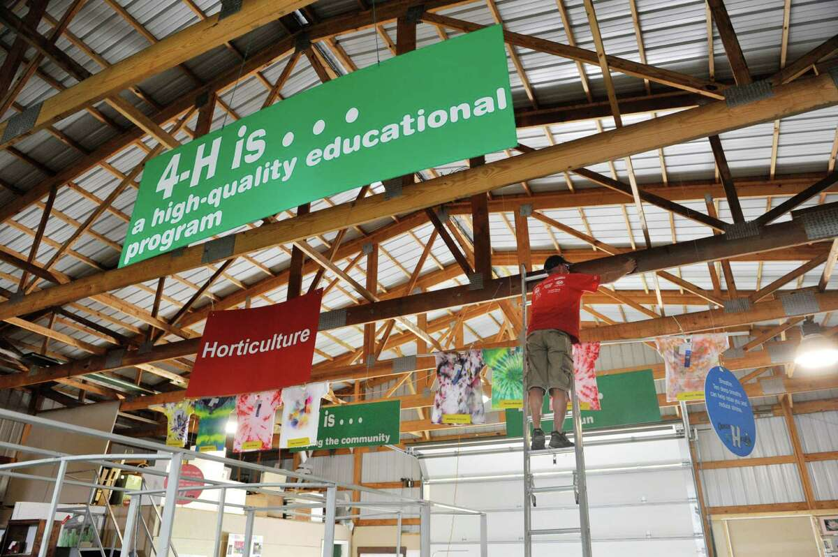 Greg Stevens of Greenfield, a Saratoga County Extension educator, hangs up a pole holding a group of T-shirts designed by children in the 4-H as setup continues for the Saratoga County Fair on Monday, July 21, 2014, in Ballston Spa, N.Y. The fair opens on Tuesday. (Paul Buckowski / Times Union)