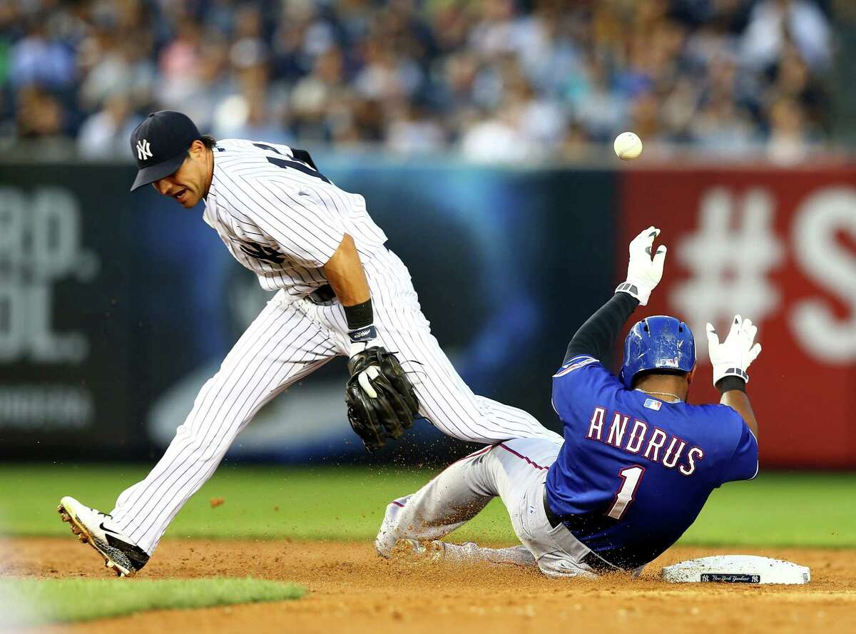 NEW YORK, NY - JULY 21: Elvis Andrus #1 of the Texas Rangers makes it to second safely as Brian Roberts #14 of the New York Yankees drops the ball on July 21, 2014 at Yankee Stadium in the Bronx borough of New York City. (Photo by Elsa/Getty Images) ORG XMIT: 477586579