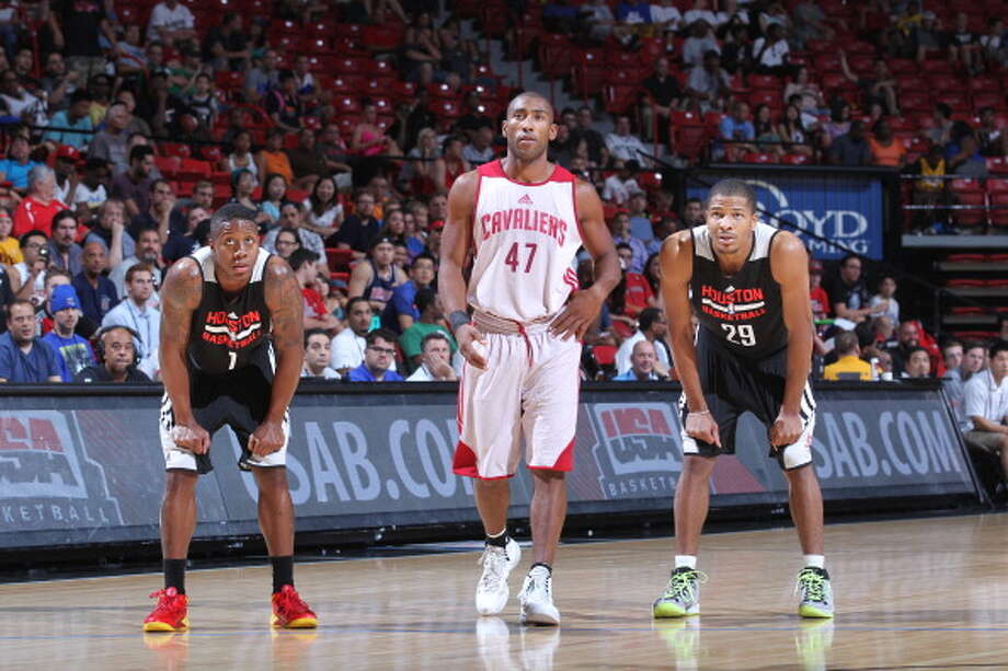 Isaiah Canaan, left, and Geron Johnson, right,  stand with Jayson Granger, center, during a free throw. Photo: Jack Arent, NBAE/Getty Images / 2014 NBAE