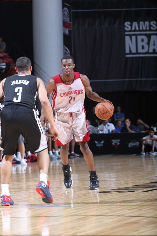 Andrew Wiggins handles the ball against Nick Johnson. Photo: Jack Arent, NBAE/Getty Images / 2014 NBAE
