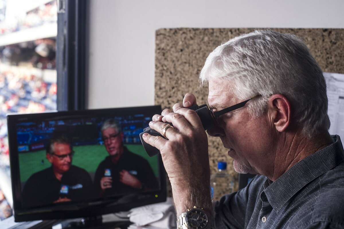 Mike Krukow, long-time television color commentator for the San Francisco Giants, looks through binoculars before the start of the game at Citizen's Bank Park in Philadelphia, PA, on July 21, 2014.