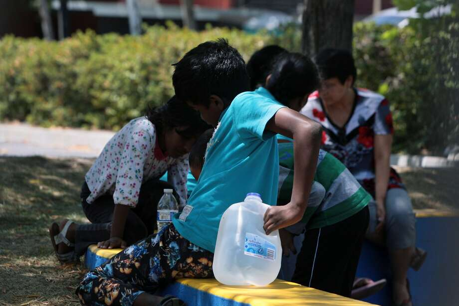 A child holds a full water container at a playground in the Springhouse Apartment complex, where residents have gone without water for four days because of a water main break, on Monday, July 21, 2014 in Pleasanton, Calif. Photo: Kevin N. Hume, The Chronicle