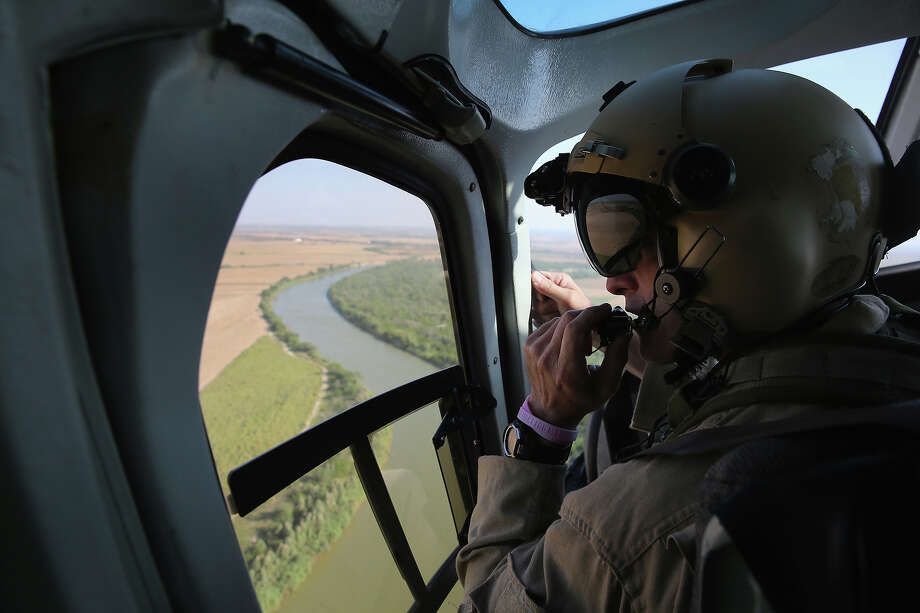 A U.S. Office of Air and Marine helicopter patrols over the Rio Grande on July 21, 2014 at the U.S.-Mexico border in McAllen, Texas. Thousands of immigrants, many of them minors from Central America, have crossed illegally into the United States this year, causing an unprecedented humanitarian crisis on the U.S.-Mexico border. Texas Governor Rick Perry announced that he will send 1,000 National Guard troops to help stem the flow. Photo: John Moore, Getty Images / 2014 Getty Images