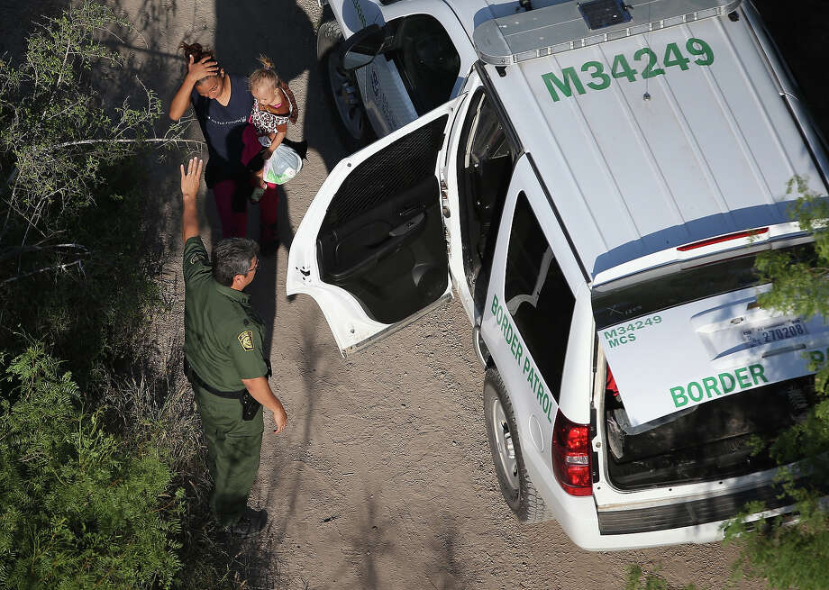 U.S. Border Patrol agents take undocumented immigrant families into custody on July 21, 2014 in McAllen, Texas. Thousands of immigrants, many of them minors from Central America, have crossed illegally into the United States this year, causing an unprecedented humanitarian crisis on the U.S.-Mexico border. Texas Governor Rick Perry announced that he will send 1,000 National Guard troops to help stem the flow. Photo: John Moore, Getty Images / 2014 Getty Images