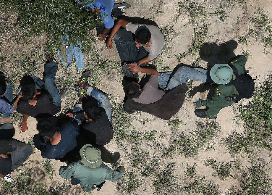 U.S. Border Patrol agents take undocumented immigrants into custody on July 21, 2014 in McAllen, Texas. Thousands of immigrants, many of them minors from Central America, have crossed illegally into the United States this year, causing an unprecedented humanitarian crisis on the U.S.-Mexico border. Texas Governor Rick Perry announced that he will send 1,000 National Guard troops to help stem the flow. Photo: John Moore, Getty Images / 2014 Getty Images