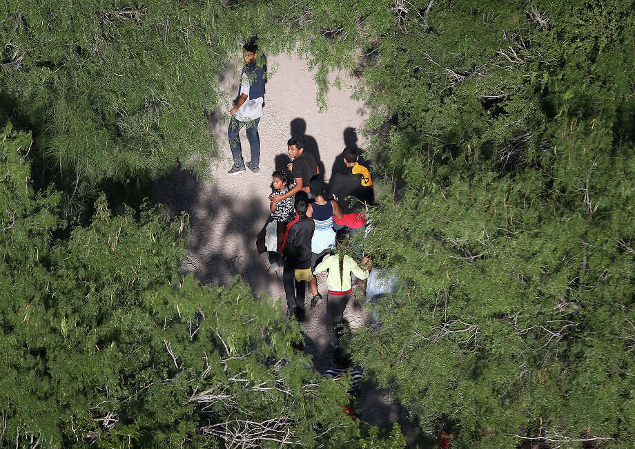 Undocumented immigrant families walk before being taken into custody by Border Patrol agents on July 21, 2014 near McAllen, Texas. Thousands of immigrants, many of them minors from Central America, have crossed illegally into the United States this year, causing an unprecedented humanitarian crisis on the U.S.-Mexico border. Texas Governor Rick Perry announced that he will send 1,000 National Guard troops to help stem the flow. Photo: John Moore, Getty Images / 2014 Getty Images