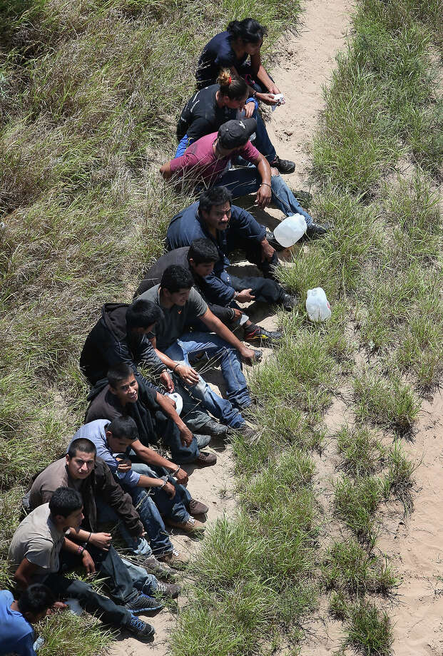 U.S. Border Patrol agents take undocumented immigrants into custody on July 21, 2014 near Falfurrias, Texas. Thousands of immigrants, many of them minors from Central America, have crossed illegally into the United States this year, causing an unprecedented humanitarian crisis on the U.S.-Mexico border. Texas Governor Rick Perry announced that he will send 1,000 National Guard troops to help stem the flow. Photo: John Moore, Getty Images / 2014 Getty Images