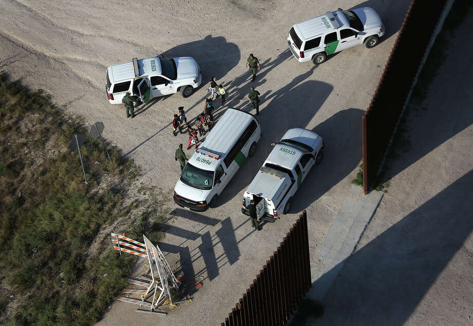 U.S. Border Patrol agents take undocumented immigrant families into custody at the border fence on July 21, 2014 in McAllen, Texas. Thousands of immigrants, many of them minors from Central America, have crossed illegally into the United States this year, causing an unprecedented humanitarian crisis on the U.S.-Mexico border. Texas Governor Rick Perry announced that he will send 1,000 National Guard troops to help stem the flow. Photo: John Moore, Getty Images / 2014 Getty Images