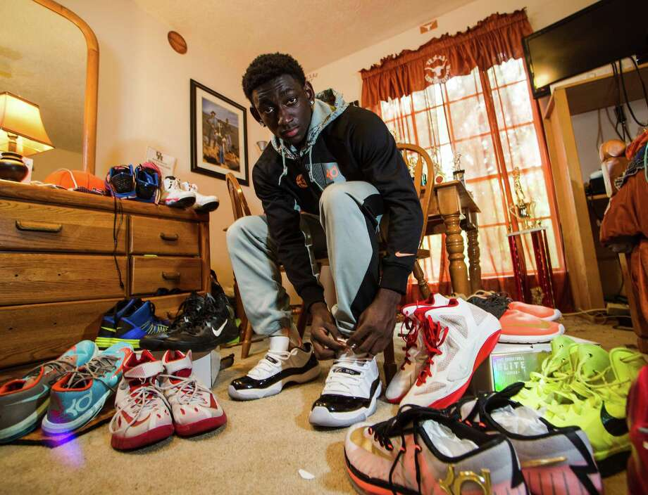 Jordan Hunter, an Ozen basketball player and sneaker aficionado, poses for a picture with a collection of his sneakers at his home Wednesday afternoon. Hunter, like some other athletes, has multiple pairs of sneakers. Photo taken Wednesday 7/9/14 Jake Daniels/@JakeD_in_SETX Photo: Jake Daniels / ©2014 The Beaumont Enterprise/Jake Daniels