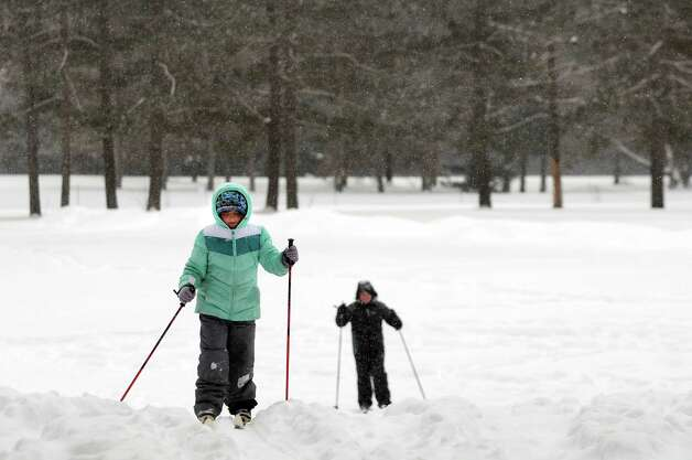 Catherine Darcy, 10, of Saratoga Springs, left, cross country skis with her father, Bill Darcy, on Tuesday, Feb. 18, 2014, at Saratoga Spa State Park in Saratoga Springs, N.Y. (Cindy Schultz / Times Union) Photo: Cindy Schultz, Albany Times Union / 00025800A