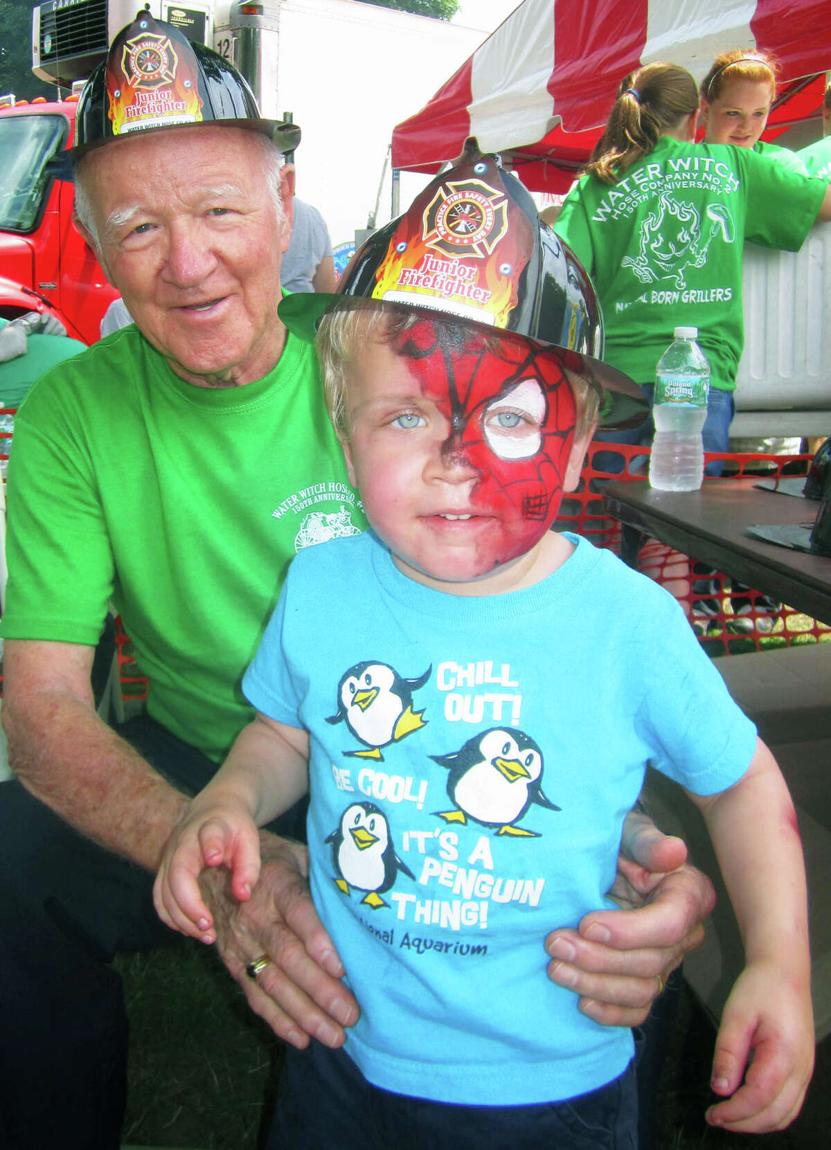 """Among the younger """"fire chiefs"""" on hand last summer for the Greater New Milford Chamber of Commerce's 46th annual Village Fair Days was C.J. Dempsey, 4, of Danbury, posing here with a real life former fire chief, Paul Hulton, 88, who served ably as Water Witch Hose Co. No. 2's chief back before C.J.'s parents were born."""