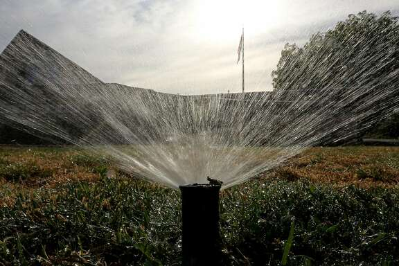 Sprinklers water a lawn Tuesday morning,  July 15, 2014, in Sacramento, Calif.  In an effort to force the public to conserve water, the State Water Resources Control Board voted 4-0 to approve a proposal that includes fines up to $500 a day for people who waste water on landscaping, fountains, washing vehicles and other outdoor uses. (AP Photo/Rich Pedroncelli)