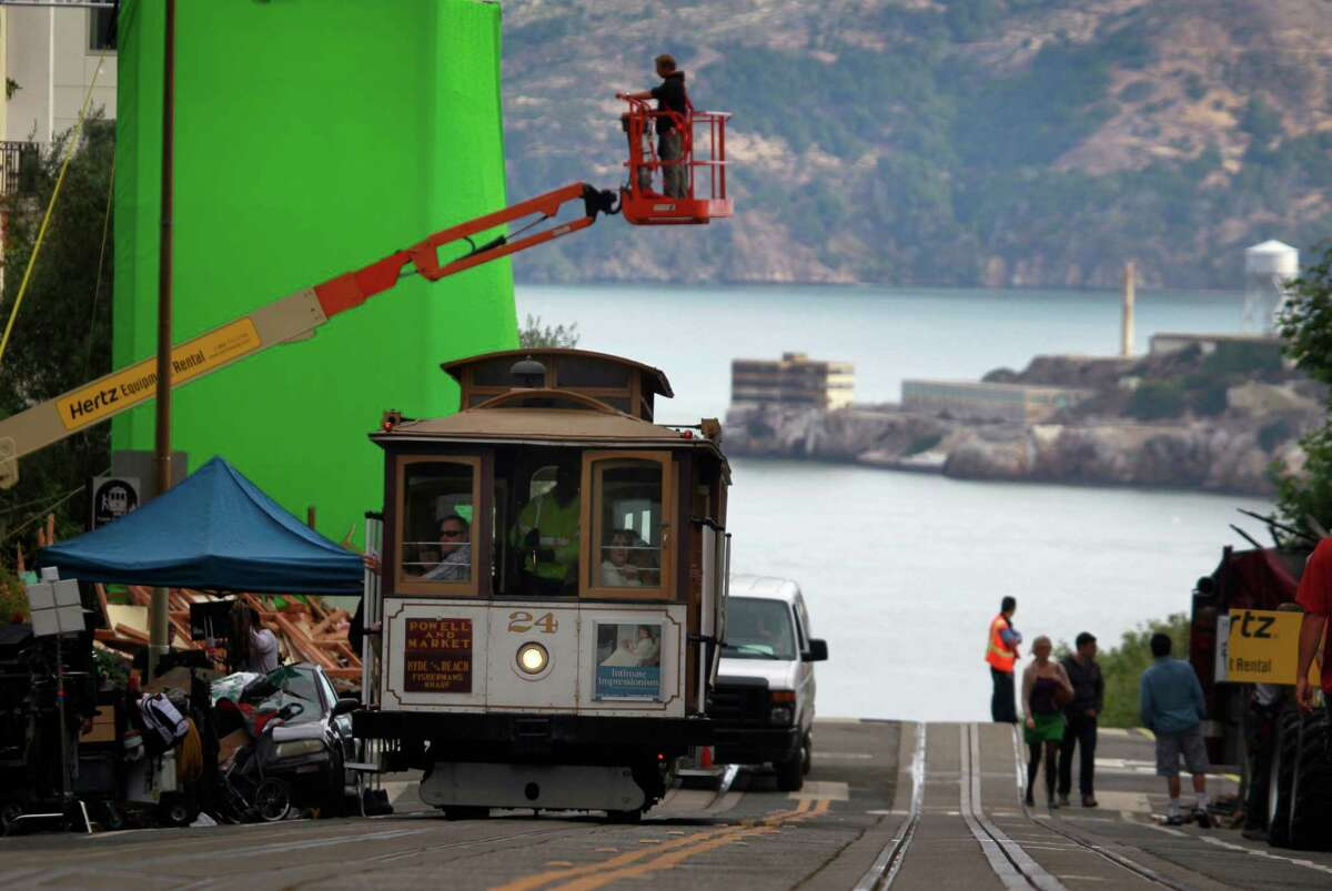 A cable car rolls through the film set where a production crew prepares to shoot a scene for the film