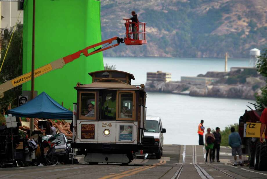 "A cable car rolls through the film set where a production crew prepares to shoot a scene for the film ""San Andreas"" on Hyde Street in San Francisco, Calif. on Tuesday, July 22, 2014. Actor Dwayne Johnson stars in the earthquake disaster movie. For more movies that destroy S.F., click through the slideshow. Photo: Paul Chinn / The Chronicle / ONLINE_YES"