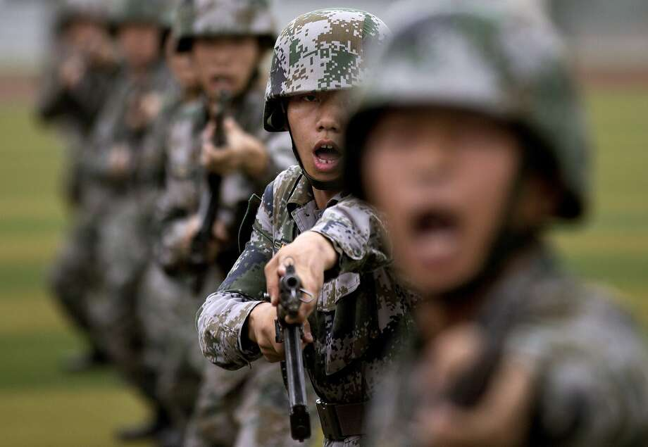 Spear-the-air day in Beijing:Chinese army cadets shout as they thrust their bayonets during a drill at the PLA's Armored Forces Engineering Academy Base on the outskirts of Beijing. Photo: Andy Wong, Associated Press