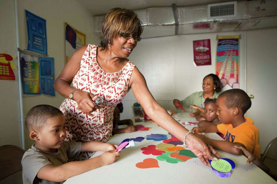 Instructor Shirley McQueen helps Michael Gonzalez, left, during arts and crafts during an evening vacation bible school at Brown Chapel A.M.E. on Monday, July 21, 2014, in Houston. Photo: J. Patric Schneider, For The Chronicle / © 2014 Houston Chronicle