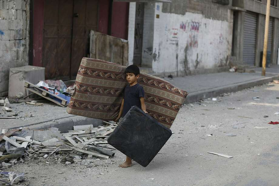 Back for his bed: A Palestinian boy carries a mattress and a cushion he recovered from his family's damaged apartment on a deserted street Gaza City. Israeli airstrikes continued to pummel the city. Photo: Mohammed Abed, AFP/Getty Images
