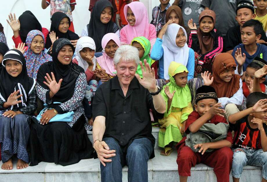 Charming the world, post-presidency: Bill Clinton  and Indonesian kids  sit for photo shoot in  Banda Aceh, Indonesia. Americans, too, seem to have an affinity for the adroit, charming pol. Photo: Heri Juanda / Associated Press / AP