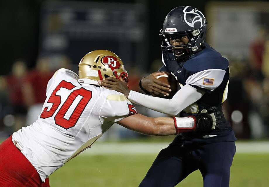 Second Baptist's Lynnard Rose (22) tries to escape the grip of  Pope John's Hunter Mills (50) as the two teams faced off at Second Baptist School in Houston on October 4, 2013. Photo: Diana L. Porter, Freelance / © Diana L. Porter