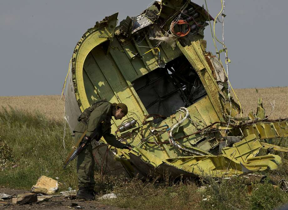 A pro-Russian rebel touches wreckage at the plane crash site near the eastern village of Hrabove. Photo: Vadim Ghirda, Associated Press