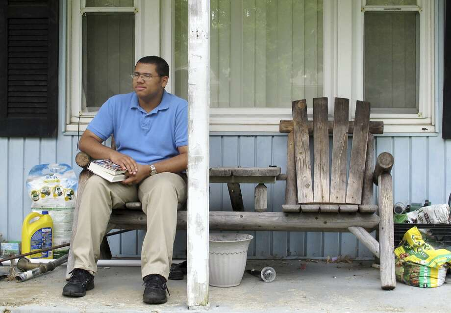 David Vernon, 18, takes a break while reading on his porch in Columbus, Ohio, on Monday, July 21, 2014. Both Republicans and Democrats are seeking voters like Vernon, a self-described moderate and an avid social media user who says he has seen a steady increase in tweets from both parties aimed at attracting younger African-American voters to get involved in political campaigns. (AP Photo) Photo: Uncredited, Associated Press