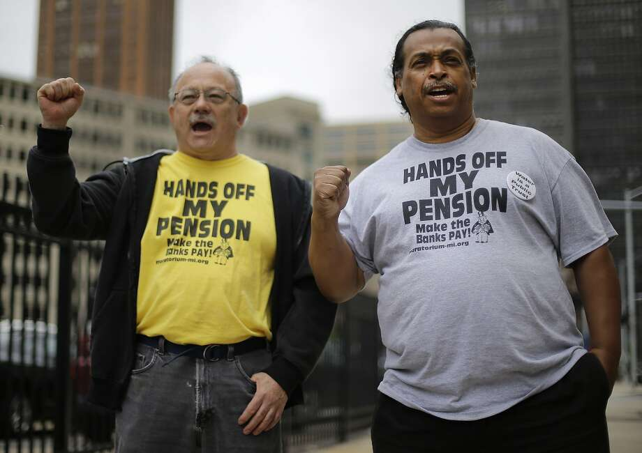 Detroit retirees Mike Shane (left) and William Davis protest July 3 near the federal courthouse in Detroit, during a 60-day period of voting by city workers and retirees on cutting their pensions. Photo: Paul Sancya, Associated Press